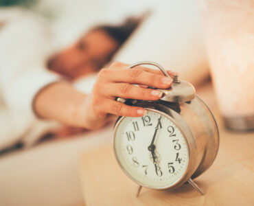 Beautiful young woman sleeping in bed and holding hand on alarm clock. Selective focus. Focus on foreground, on clock.