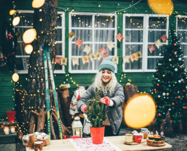 Woman decorating home for Christmas and hanging baubles on Christmas tree outside.