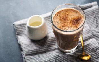 Tasty chai latte in glass on dark background.