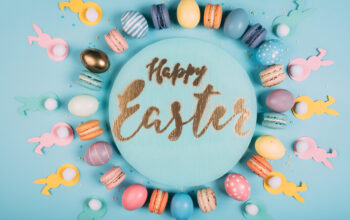 top view of round board with happy easter lettering and colorful easter decor around on blue surface
