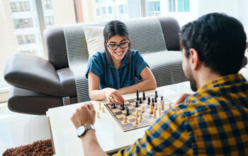 Young people playing chess game for brain training. Happy boyfriend and girlfriend having fun at home.