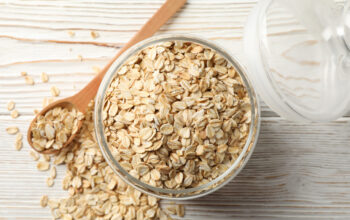 Glass jar with oatmeal and spoon on wooden background, top view