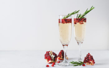 Pomegranate champagne rose with rosemary in tall glass on white background, copy space