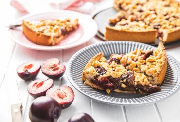 Sweet plum pie. Cut pieces of pie on plate.