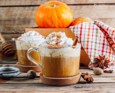 Pumpkin spiced latte in a glass mug on a vintage wooden background. Autumn or winter hot drink. Selective focus